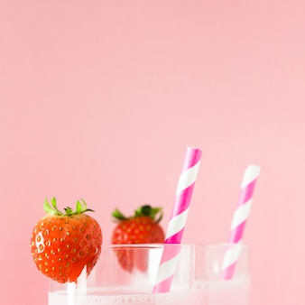 Close-up of milkshakes with strawberries and straws