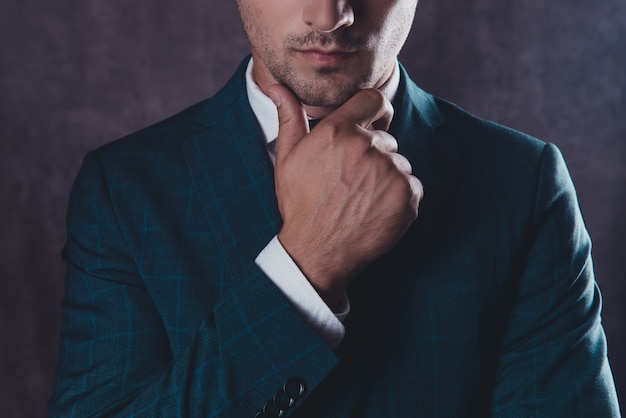 Close up of minded young businessman  touching his face