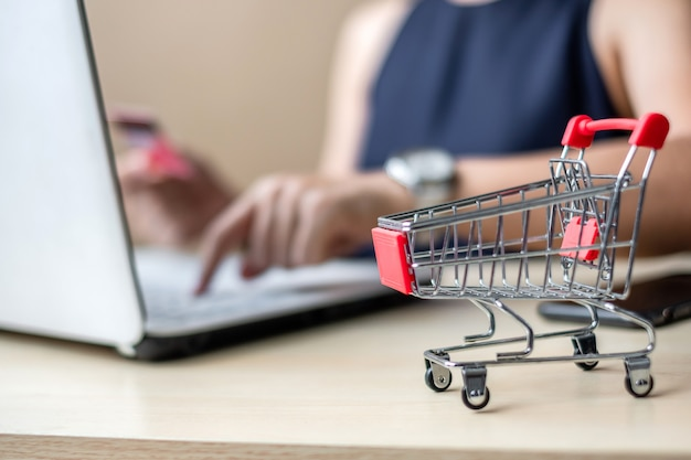 Close up mini cart, asian businesswoman holding credit card and using laptop