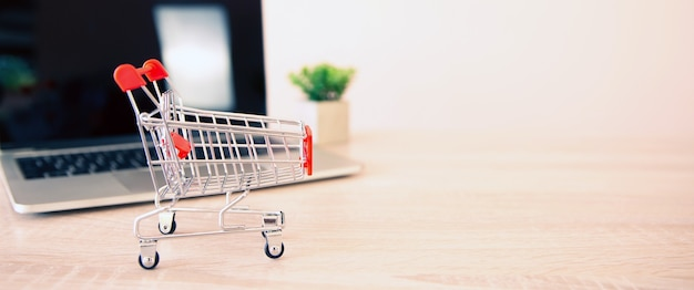 Close up the mini shopping cart and laptop at desk.