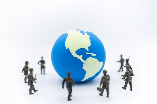 Close up of mini world ball with group of soldier miniature figure standing around.