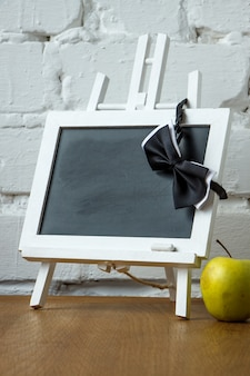 Close-up of a miniature chalk board, bow tie and apple