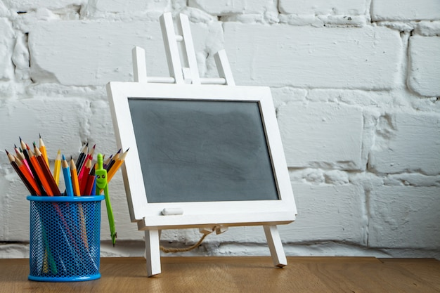 Close-up miniature chalk board and stand with school stationery on a white brick wall
