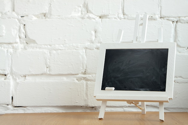 Close-up of a miniature chalk board with chalk stains and chalk on a white brick wall