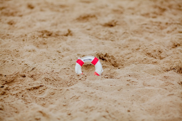 Close-up of miniature lifebuoy dig in the sand at beach