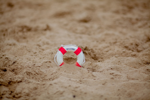 Close up of miniature lifebuoy on the sand
