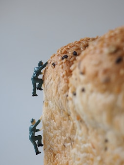 Close up miniature people many of worker man working on whole grain bread background