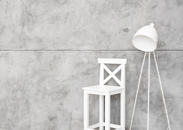 Close-up minimalist white floor lamp and stool with concrete panels
