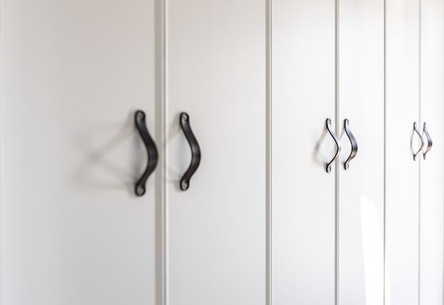 Primo piano di mobili bianchi minimalisti con dettagli dell'armadio da cucina con maniglie nere