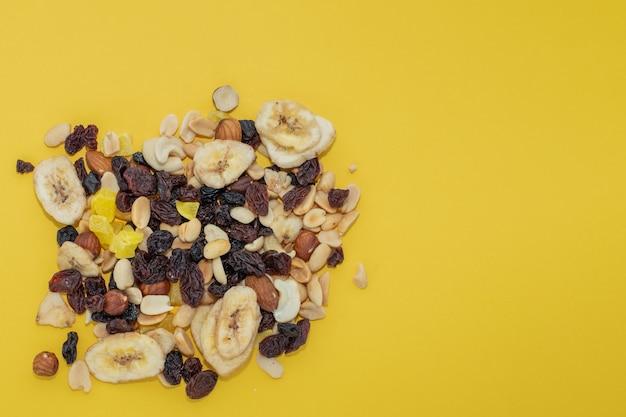 黄色の背景にクローズアップミックスナッツとドライフルーツ、コピースペース。食事療法、適切な栄養の概念。