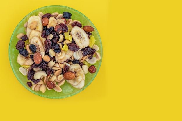 緑の皿の黄色のクローズアップミックスナッツとドライフルーツ、コピースペース。