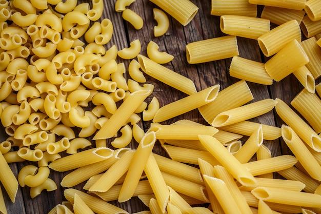 Закройте вверх по смеси сырых сушеных макаронных изделий talian, макарон, спагетти, деревянного стола penne om. вид сверху