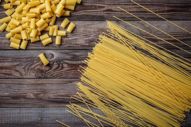 Закройте вверх по смеси сырых сушеных макарон, макарон, спагетти, пенне на деревянном столе. вид сверху