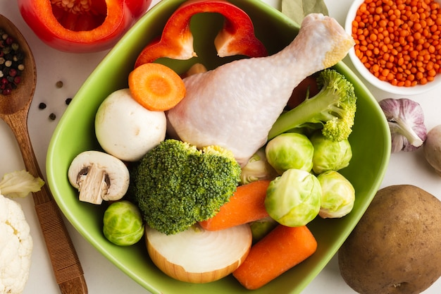 Close-up mix of vegetables in bowl with chicken drumstick