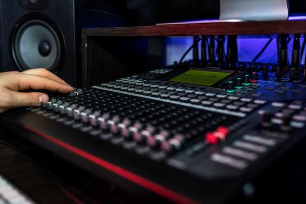 작곡가가 새로운 믹스를 연주하는 레코드 스튜디오에서 믹서를 닫습니다. 악기 사진.