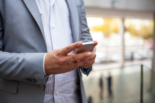 Close-up of mobile phone in hands of businessman