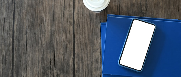 Close up on mobile phone with white screen, notebook  on wooden table