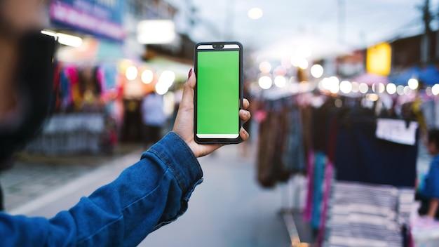 タイを歩くために夜のストリートマーケットで握っている手の緑色の画面で携帯電話を閉じます。
