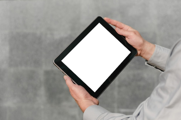 Close up, mock up tablet, in hands, of a person. against the background of a concrete wall.