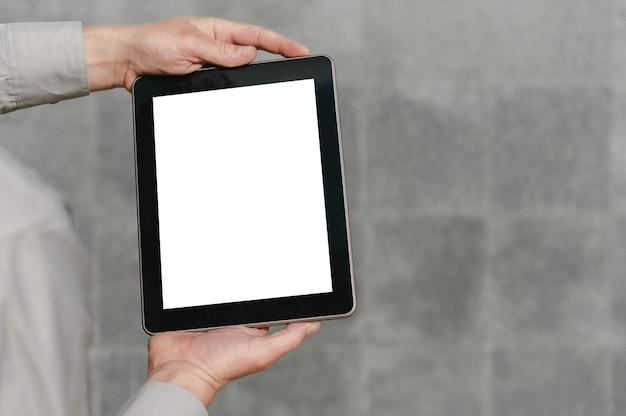 人の手でタブレットをクローズアップ、モックアップします。コンクリートの壁を背景に。