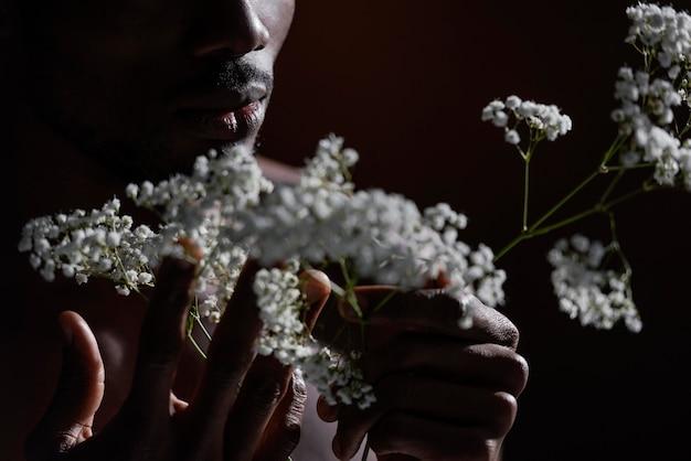 Макро модель держит цветы в темноте