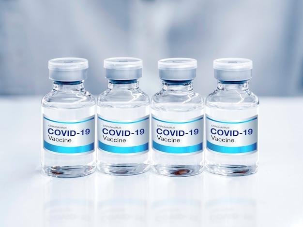 ラボのテーブルにある4つのボトルバイアルにモダンなブルーラベルのcovid19ワクチンをクローズアップ