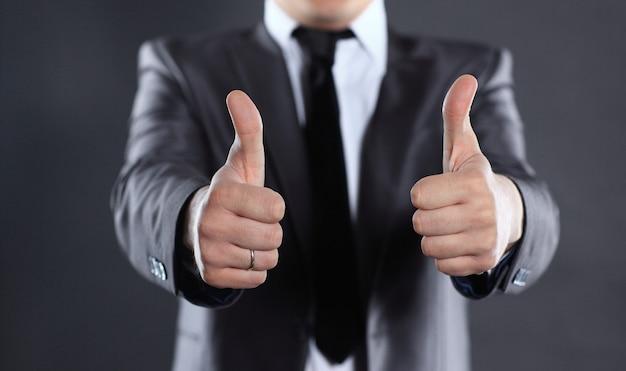 クローズアップ。親指を立てている現代のビジネスマン。黒に分離