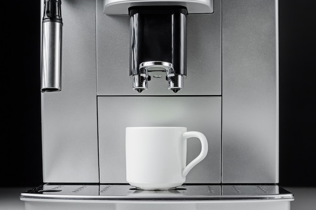 Close up of modern coffee machine and white cup