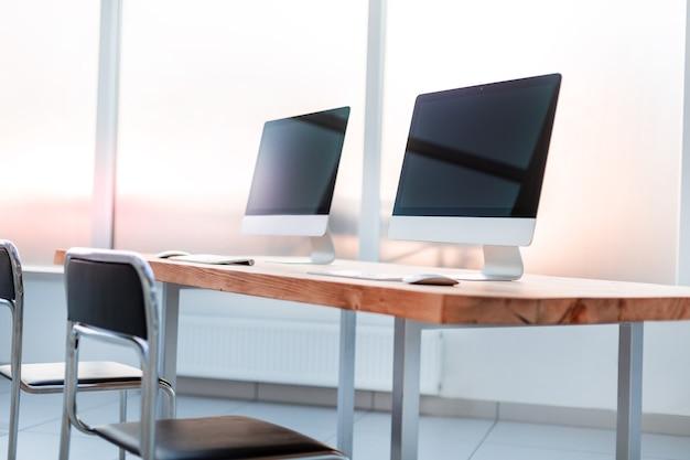 閉じる。木製のテーブルの上の現代のコンピュータ。ビジネスコンセプト