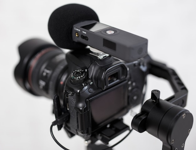 Close up of modern dslr camera on 3-axis gimbal stabilizer with microphone recorder over gray background