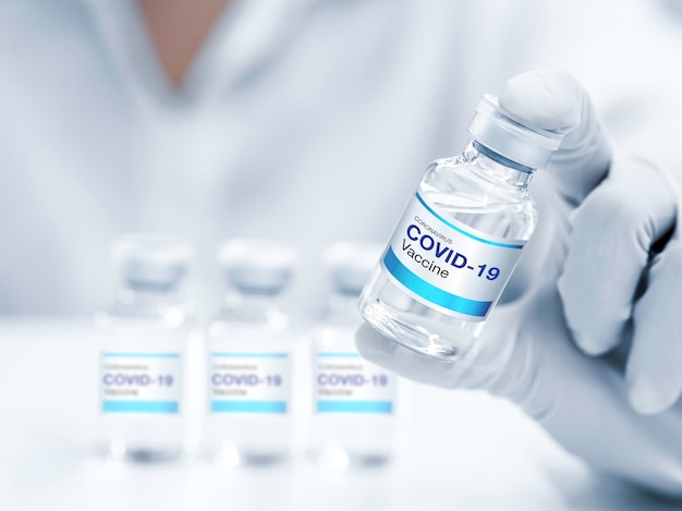 ラボで手袋を着用している科学者または医師の手によって示されているボトルバイアル上の最新のラベルcovid19ワクチンをクローズアップ