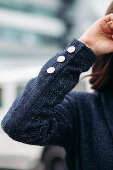 Primo piano di una donna moderna con un'elegante giacca nera che tiene la mano in alto e in piedi in città. copia spazio