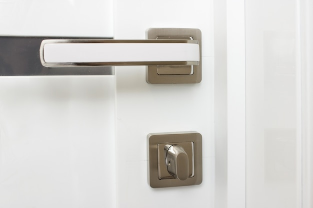 Close - up of a modern metal handle on a white wooden door.