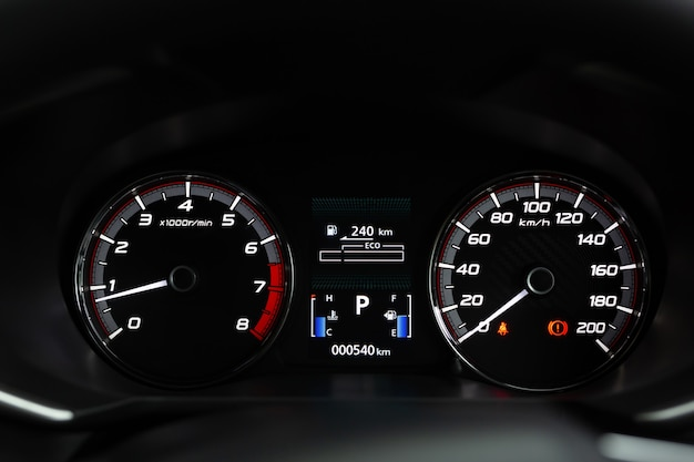 Close up modern mileage car dashboard instrument panel interior with warning lights, seat belts and handbrake lights
