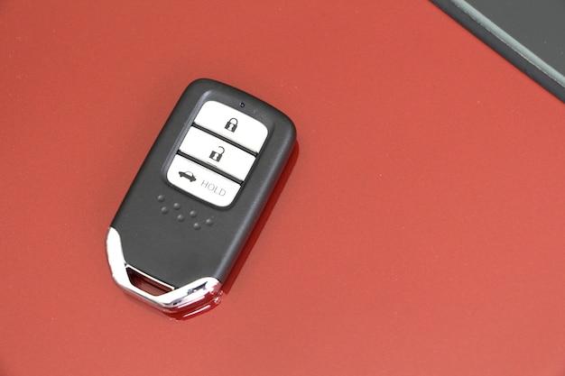 Закройте вверх по современному дистанционному управлению автомобилем или ключом от машины на металлическом фоне автомобиля.