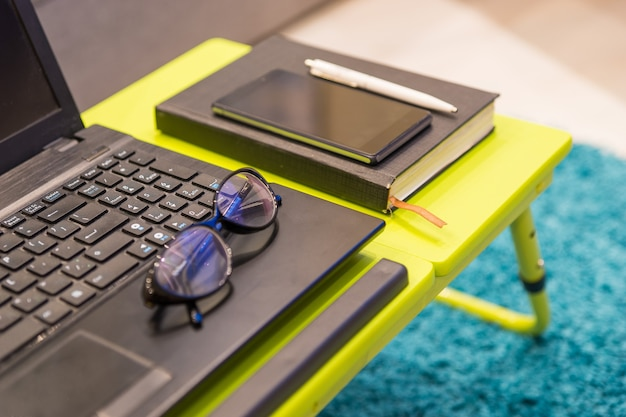 Close up of a modern tabletop workstation with stylish eyeglasses lying on the keyboard of an open laptop computer with a diary and mobile phone alongside