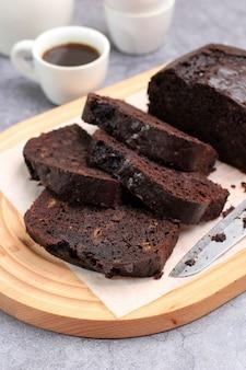 Закройте влажный шоколадно-банановый торт на белой тарелке, скопируйте пространство для текста, рецепта и рекламы.