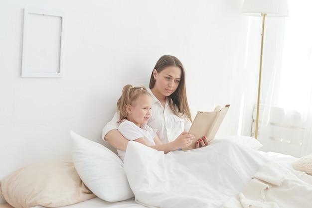 Крупным планом мама и дочка отдыхают в уютной постели, вместе читают забавную интересную детскую книжку.
