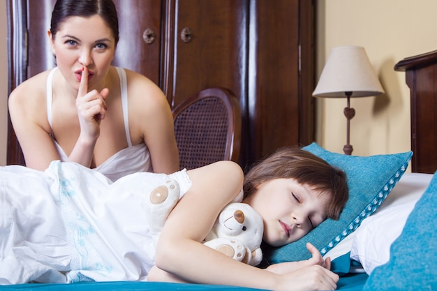 Close up mom and daughter in bedroom mother showing hash sign at camera daughter closed eyes and