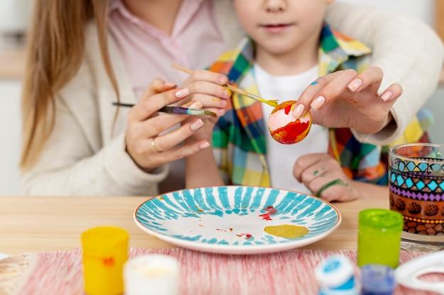 Крупным планом мама помогает сыну красить яйца