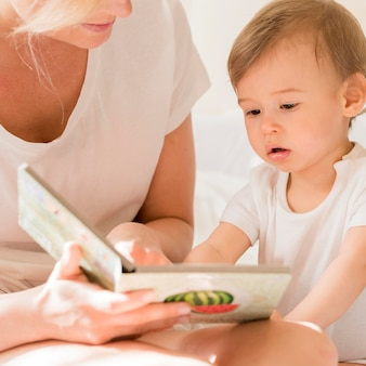 Close-up mom reading to baby in bed