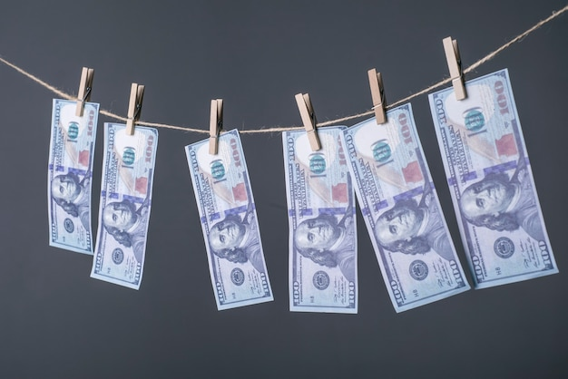 Close-up of money, dried on the ropes, fastened with clothespins. the concept of drying money.
