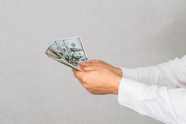 Крупный план деньги в руках мужчины. на светлом фоне.