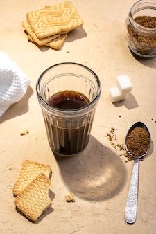木製のテーブルに鉄のスプーンとクッキーで朝のインスタントコーヒーを閉じる