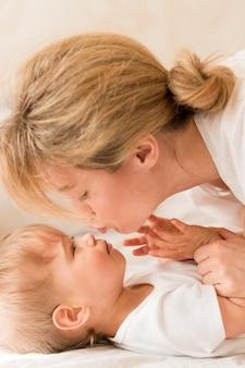 クローズアップの母親と赤ちゃんがベッドで寄り添う