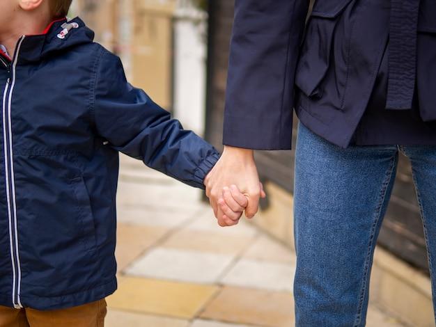 Макро мать и сын, держась за руки