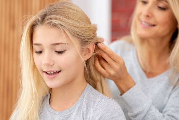 Close-up mother braiding daughter hair