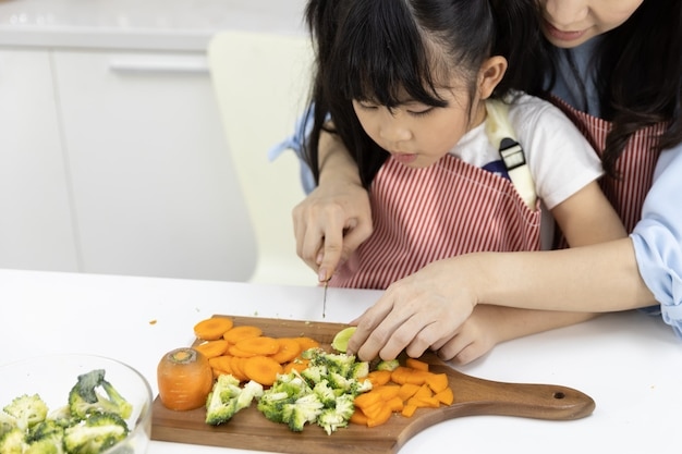 Close up of mother and daughter cutting vegetables