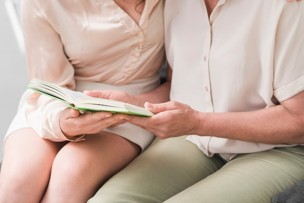 Primo piano del libro della tenuta della madre e della figlia