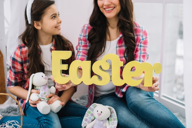 Close-up of mother and daughter holding bunny and easter word in hand